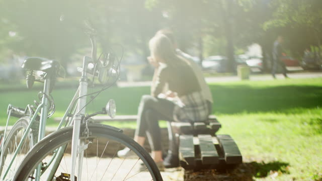 ベンチに放置自転車に座ってカップル - ベンチ点の映像素材/bロール