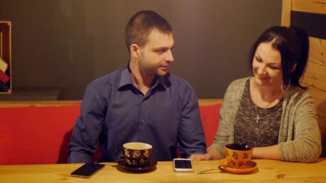 A couple sitting in a cafe, talking, drinks coffee and watching the phone video