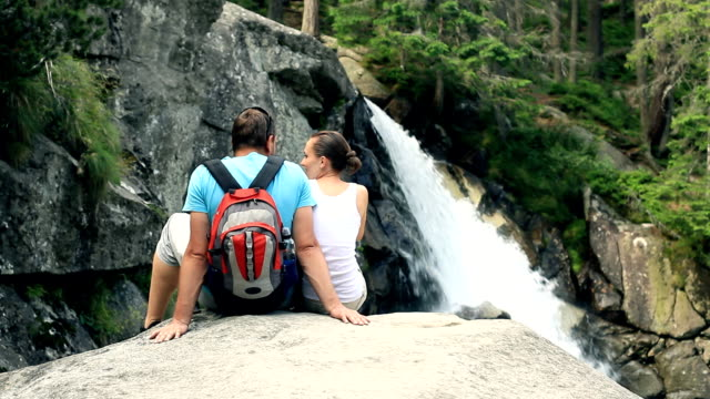 Couple sitting in front of a waterfall