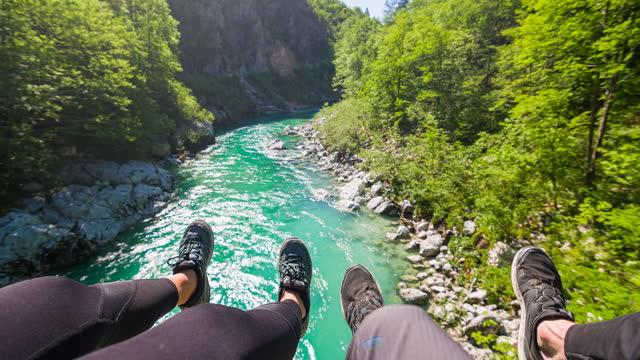 vídeos de stock, filmes e b-roll de casal sentado em uma ponte pendurada, olhando para o rio montanha abaixo, pendurado com os pés - azul turquesa