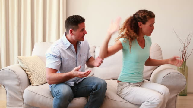 Couple sitting on couch fighting with each other video