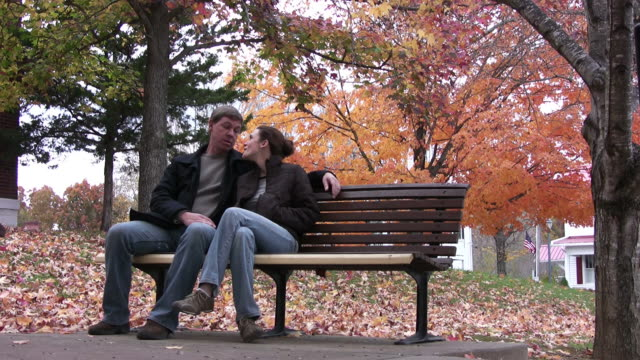 Couple sitting on park bench video