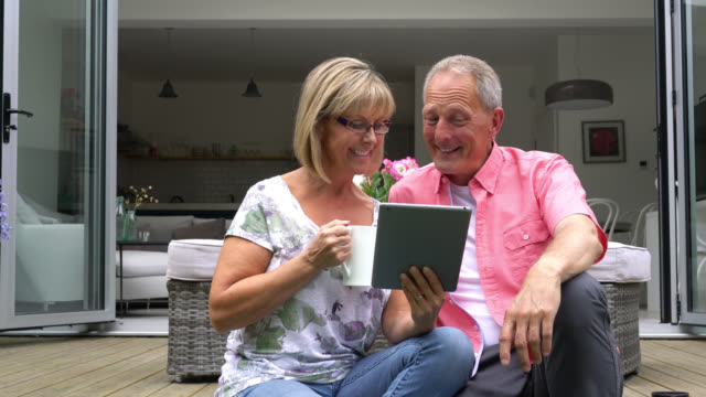 Couple sitting on porch looking at something on tablet Senior couple sitting on their porch looking at something on the tablet porch stock videos & royalty-free footage