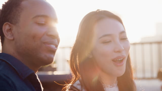 vídeos de stock, filmes e b-roll de casal que estava no terraço do último piso contra queima sol com skyline da cidade no fundo - reunião encontro social
