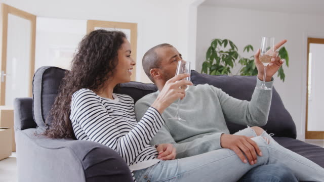 Couple sitting on sofa and celebrating with champagne as they move into new home together - shot in slow motion