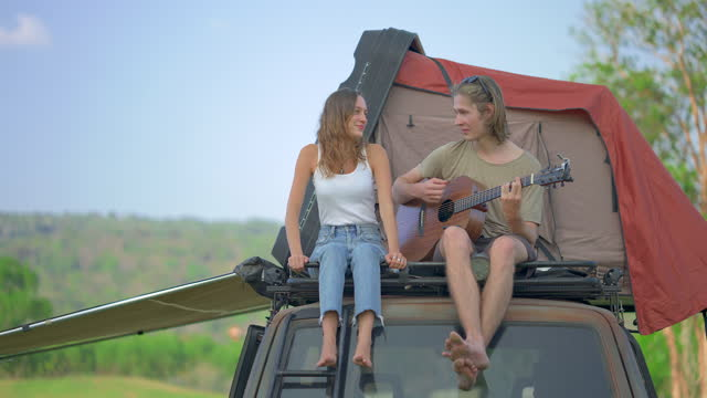 Couple sitting on the camp car roof top playing guitar and singing together