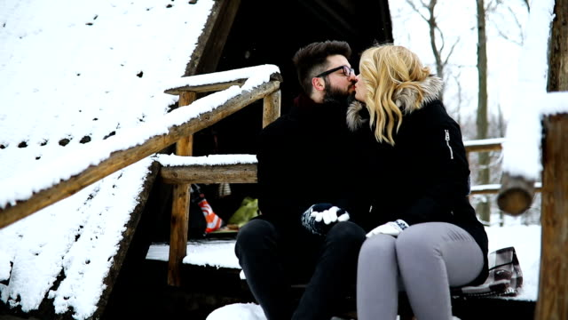 Couple sitting on wooden stairs outdoors in winter video