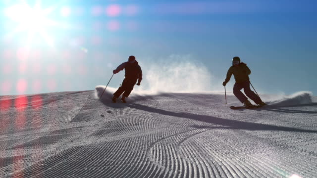 slo mo ld par skidor på en solig dag - vintersport bildbanksvideor och videomaterial från bakom kulisserna