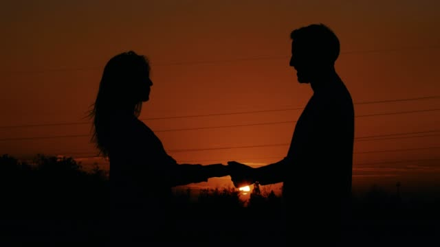 Couple spinning around at sunset, silhouettes