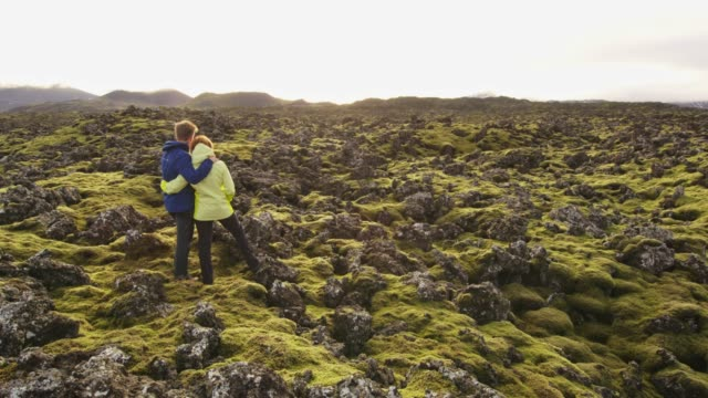 MS Couple standing among moss covered rocks in remote landscape,Iceland