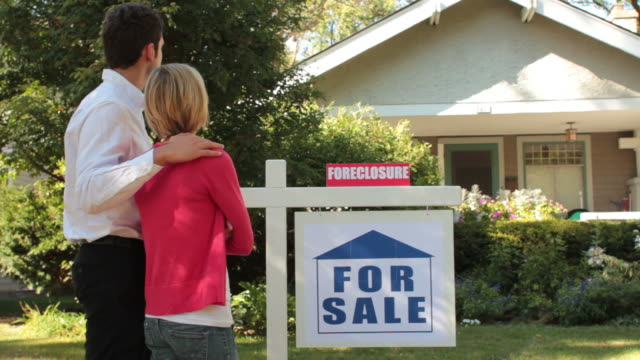 couple standing in front of their foreclosed home - foreclosure stock videos & royalty-free footage