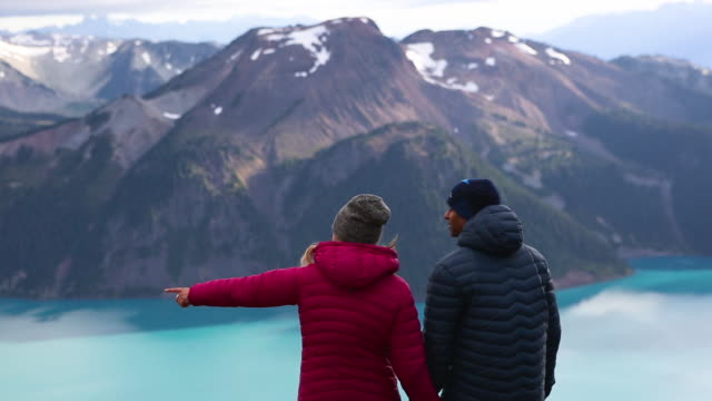 Couple standing on a mountain top looking at the beautiful view video