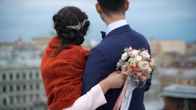 couple standing on the roof. happy bride and groom - true love angielski zwrot filmów i materiałów b-roll