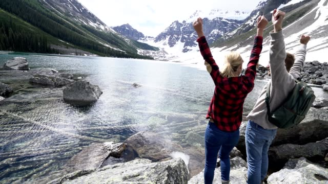 Couple stands by the lake arms outstretched in the air video