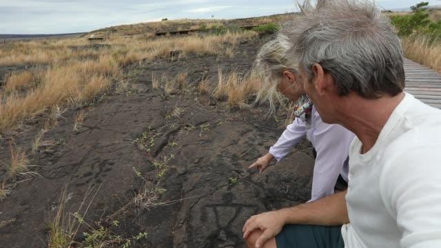 vídeos de stock, filmes e b-roll de casal parar no calçadão, olhares em petroglifos - civilização milenar