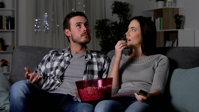 Couple suffering a blackout watching tv
