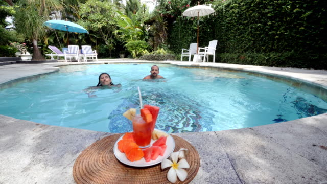 Couple swims towards a healthy snack and drink and eat in a luxury spa villa in Bali Man and woman swim in a pool, come to the camera and drink from a glass with a healthy fruity drink and eat some fruits at the pool edge in a luxury spa villa in Bali military private stock videos & royalty-free footage