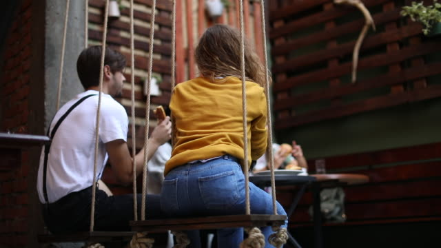 Couple Swinging Gently While eating pizza
