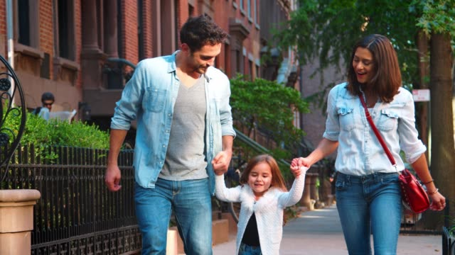 couple swinging their daughter as they walk down the street - oscillare video stock e b–roll