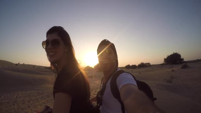 couple taking a selfie in a camel riding in desert - oman filmów i materiałów b-roll