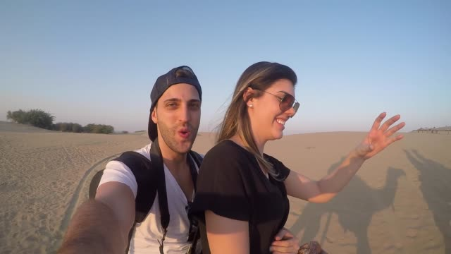 couple taking a selfie in a camel riding in desert - турист с рюкзаком стоковые видео и кадры b-roll