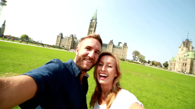 couple taking selfie in front of canadian parliament - canada travel stock videos and b-roll footage