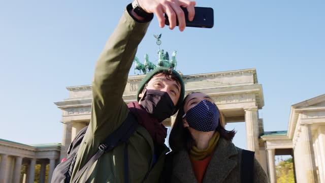 Couple taking selfie in front of famous Brandenburg Gate