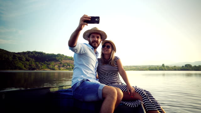 Couple taking selfie on a rowboat video