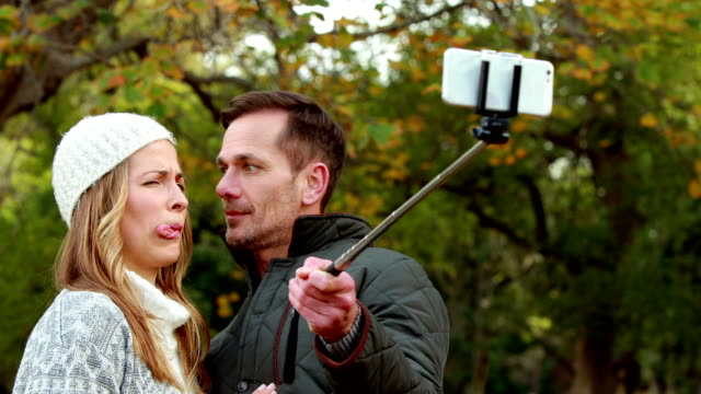 Couple taking selfie on autumns day in park video