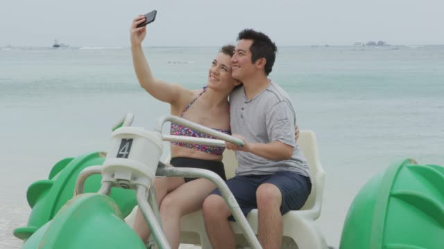 Couple taking selfie on water tricycle in Hawaii