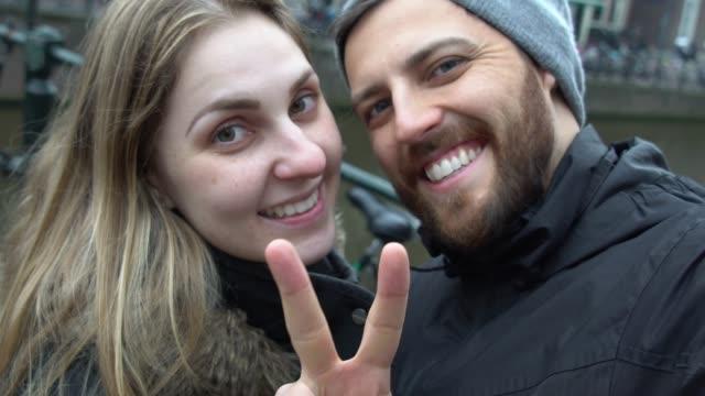 coppia che scatta foto selfie ad amsterdam, paesi bassi - relazione umana video stock e b–roll