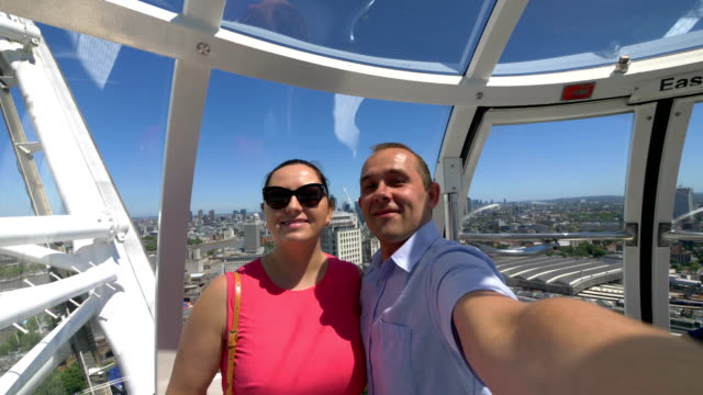 Couple taking selfie with a view of London in slow motion in 4k