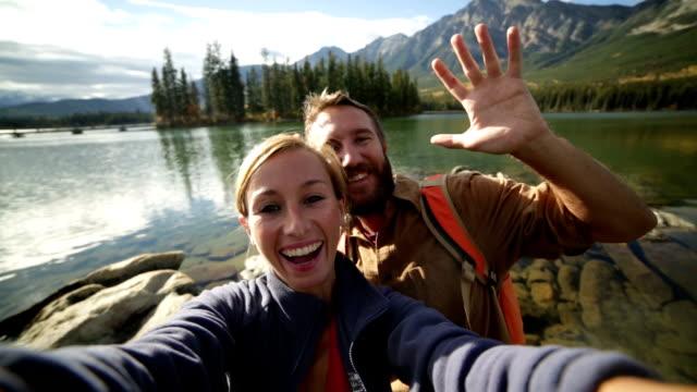Couple taking selfies by mountain lake video