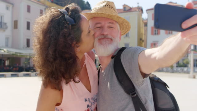 Couple taking selfies in a sunny town square