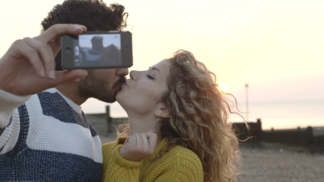 Couple taking selfin on beach with phone camera video