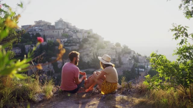 Couple talking and looking at Gordes village in Provence Young Caucasian heterosexual couple  talking and looking at Gordes village in Provence provence alpes cote d'azur stock videos & royalty-free footage