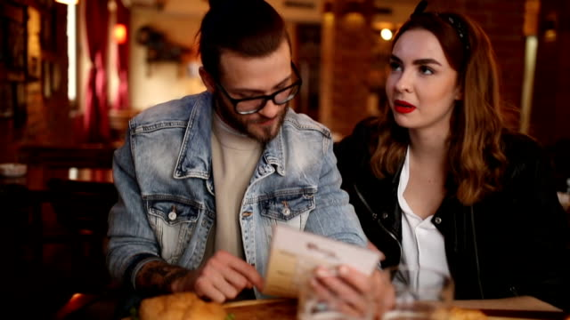Couple talking and looking into menu in a pub Couple talking and looking into menu in a pub menu stock videos & royalty-free footage
