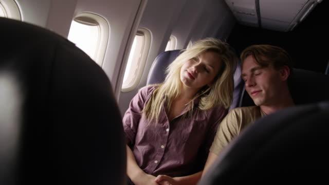 몇 가지 얘기 하 고 비행기 비행에 창 밖을 바라보 - 이성 커플 스톡 비디오 및 b-롤 화면