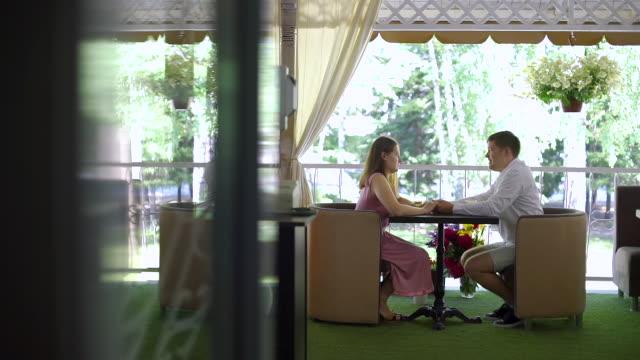 vidéos et rushes de couples parlant sur la terrasse d'été d'un café - man drinking terrace