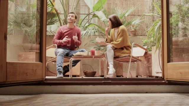 vídeos de stock e filmes b-roll de couple talking while having breakfast in yard - mesa mobília