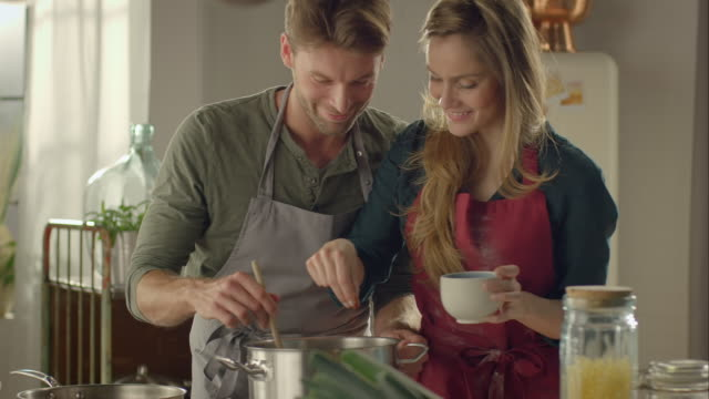 Couple tasting self-made food in the kitchen Medium shot of a couple cooking together. The woman flavors the soup with spices. Both of them taste their self-made food in a kitchen furnished in rustic style. tasting stock videos & royalty-free footage