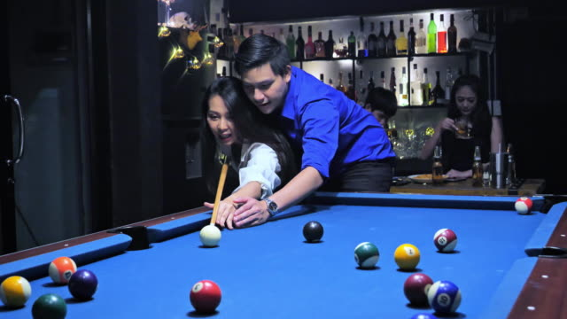 Couple teaches billiards balls are in the bar with friends, ride is fun and cheer.