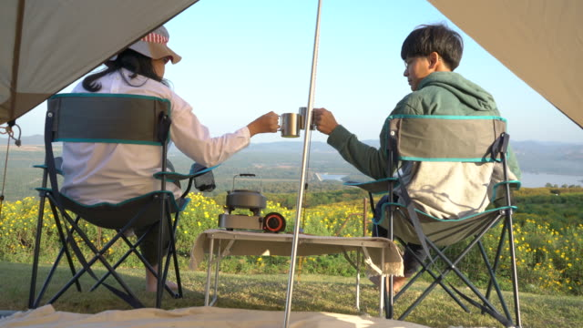 Couple toast with aluminum cups sitting in front of camping tent