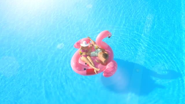stockvideo's en b-roll-footage met luchtfoto lens flare: paar roosteren en cocktails drinken op opblaasbare flamingo - opblaasband