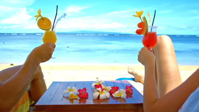 MS Couple Toasting With Cocktails On The Beach HD1080p: MEDIUM shot of a loving couple toasting with glasses of cocktails while lying on sun loungers on the beach. Sanur. Bali. Indonesia.The footage was shot in raw. Also available in 4K resolution. holiday stock videos & royalty-free footage