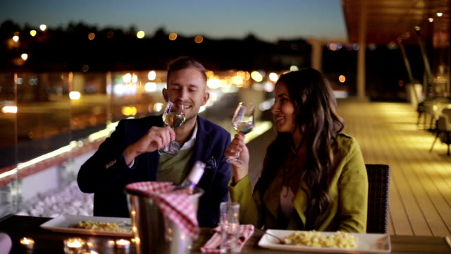 Couple toasting with wine in restaurant video