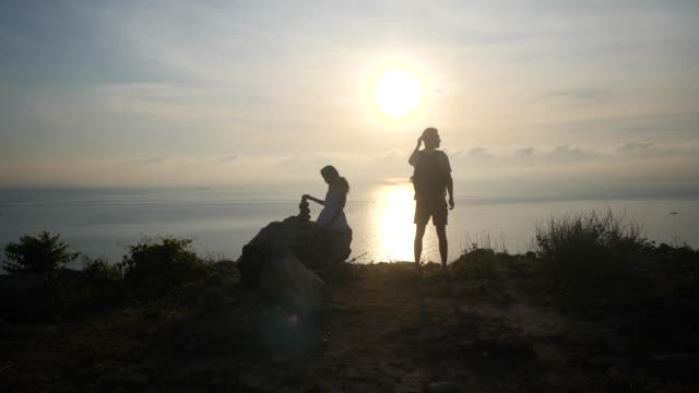 Couple traveler at a cliff with the view of sunrise and ocean horizon. Couple traveler at a cliff with the view of sunrise and ocean horizon. Man stands facing the sunrise and the ocean, young woman sitting on a rock and balancing stones. minority groups stock videos & royalty-free footage