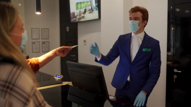 Couple travelers with medical masks on hotel reception talking to male receptionist