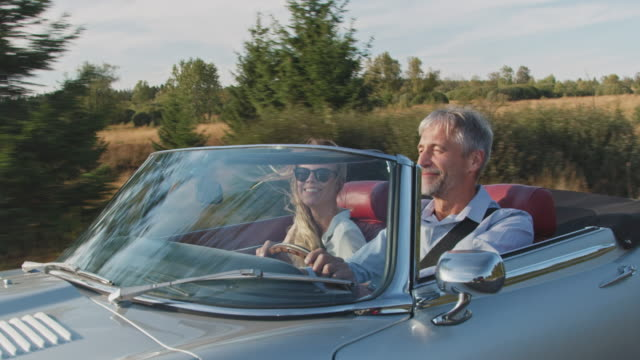 Couple traveling in classic car during windy day