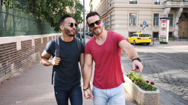 LGBT couple traveling in summer - gay vacations Gay couple enjoying city break in Europe lgbtqi rights stock videos & royalty-free footage